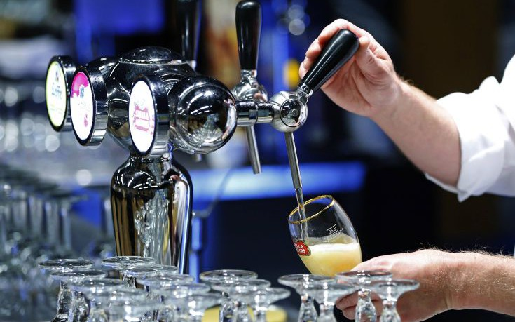 File photo of a waiter serving a glass of beer ahead of an Anheuser-Busch InBev shareholders meeting in Brussels