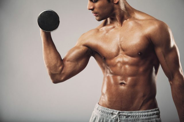 Cropped image of young muscular man doing heavy dumbbell exercise for biceps. Man working out with dumbbells on grey background. Fitness and workout concept.
