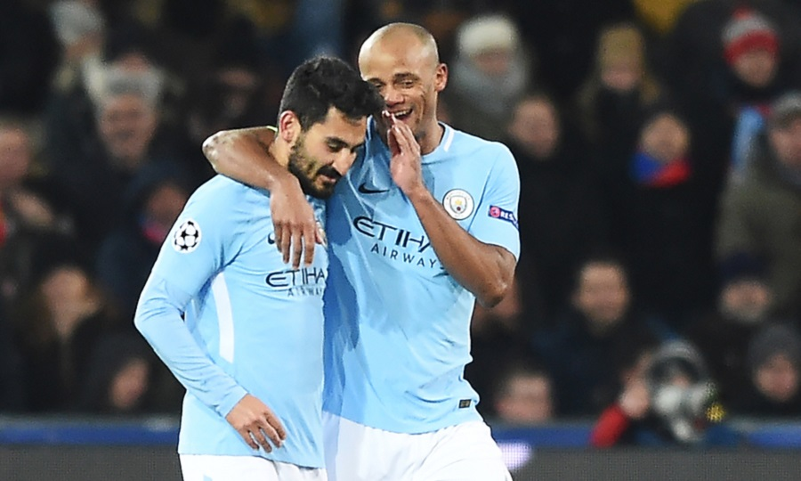 Manchester City's German midfielder Ilkay Gundogan (L) celebrates with Manchester City's Belgian defender Vincent Kompany after scoring his second goal  during the UEFA Champions League round of 16 first leg football match between Basel and Manchester City at the Saint Jakob-Park Stadium in Basel on February 13, 2018. / AFP PHOTO / SEBASTIEN BOZON        (Photo credit should read SEBASTIEN BOZON/AFP/Getty Images)